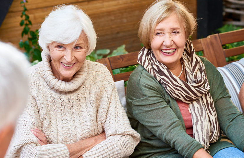 Senior women with charming smiles listening to their male friend with interest while having gathering at cozy small patio